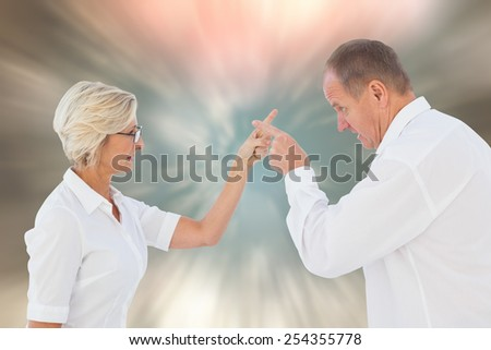Angry older couple arguing with each other against blurred christmas background - stock photo