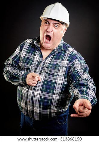 Angry overweight construction worker screaming and pointing at something - stock photo