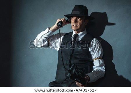 Angry retro film noir man calling with old phone.