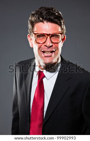 Angry screaming business man with grey suit and red tie isolated on dark background. Wearing vintage glasses. Studio shot.