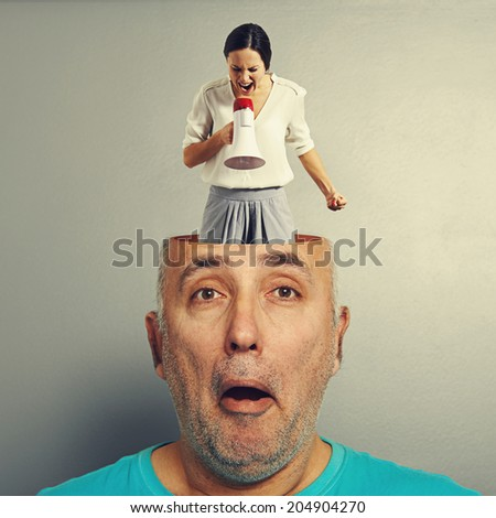 angry screaming woman in the head of amazed senior man over grey background