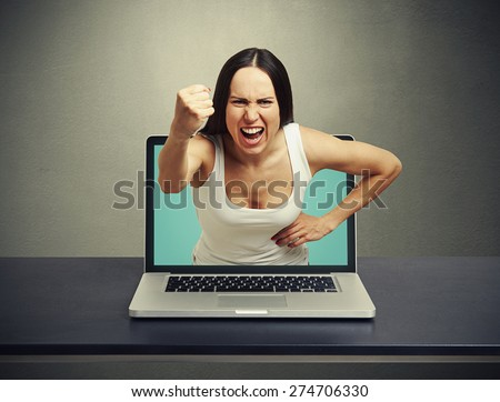angry screaming woman stretching out of laptop and showing fist at camera against dark background - stock photo