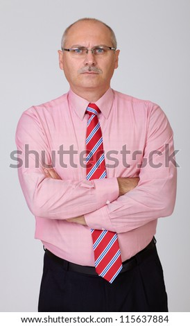 Angry senior businessman in a shirt with hands folded isolated on grey - stock photo