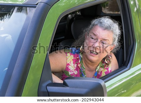 Angry senior woman driver with road rage yelling out car window.