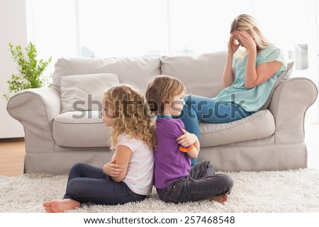 Angry siblings sitting arms crossed with upset mother on sofa at home - stock photo