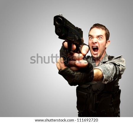 Angry Soldier Man With Gun Isolated On gray Background - stock photo
