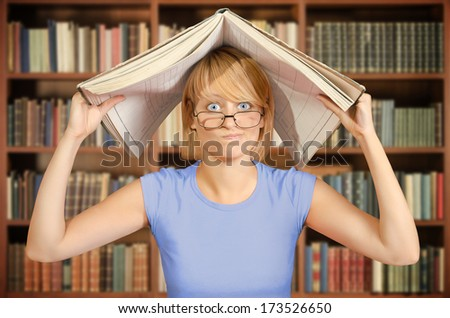 Angry student in library with an open book over her head - stock photo