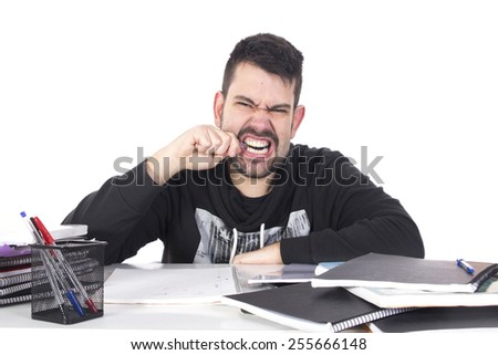 Angry student studying at table woth alot of books