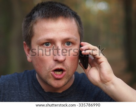 Angry surprised man with a smartphone. - stock photo