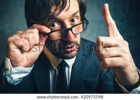 Angry tax inspector looking serious and determined, aggressive finger threatening adult businessperson with glasses - stock photo