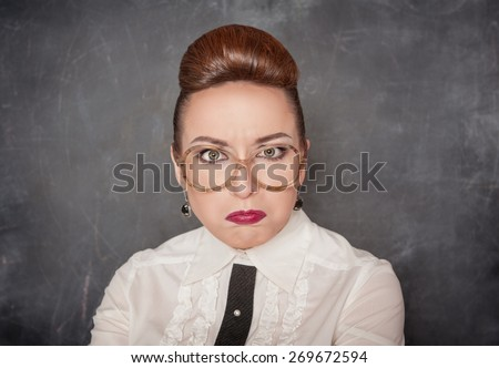Angry teacher with eyeglasses on the school blackboard background  - stock photo