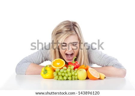 Angry teenage girl screaming out loud in front of fruits against white background - stock photo