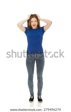 Angry teenage woman holding her head. - stock photo