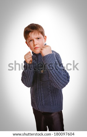 angry teenager boy clenched his fists fight isolated on white background gray - stock photo
