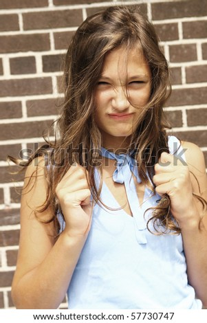 Angry teenager girl with hair in hand - stock photo