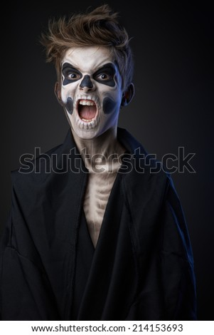 angry teenager with makeup skull cape