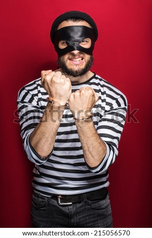 Angry thief with handcuffs. Portrait on red background   - stock photo