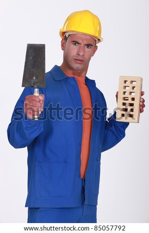Angry tradesman holding a brick and trowel - stock photo