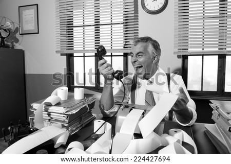 Angry vintage businessman shouting out loud at phone surrounded by adding machine tape.