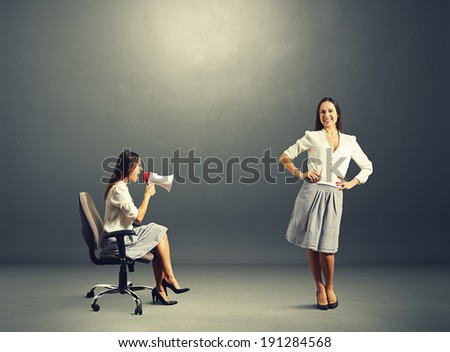 angry woman and smiley calm woman over dark background - stock photo