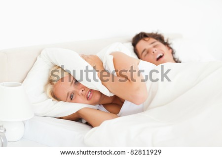 Angry woman awaken by her husband's snoring in their bedroom - stock photo