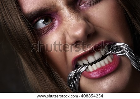 Angry Woman bite a Chain. Expressive beauty Look - stock photo