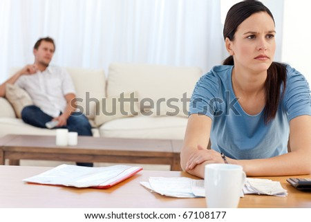 Angry woman doing her account while her boyfriend relaxing on the sofa