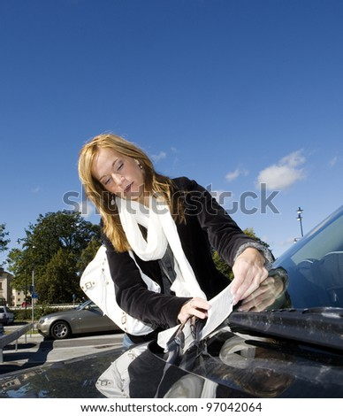 Angry woman getting a Parking Ticket - stock photo