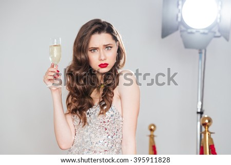 Angry woman holding glass of champagne and looking at camera