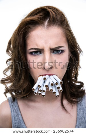 Angry woman holding many cigarettes in the mouth - stock photo