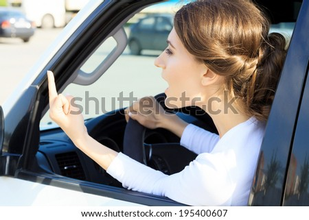 Angry woman in a car, boorishness on a road