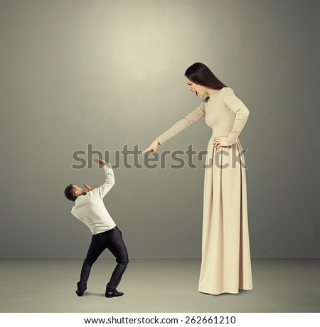 angry woman in long dress screaming at small startled man in the dark room - stock photo