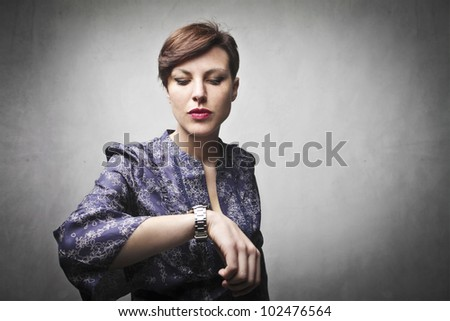 Angry woman indicating her wristwatch - stock photo
