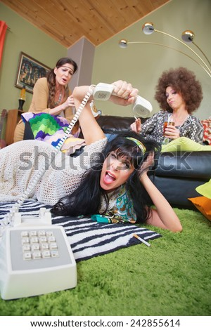 Angry woman laying on rug hanging up phone - stock photo