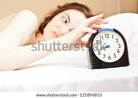 Angry woman lying a bed and holding an alarm (focus on alarm)
