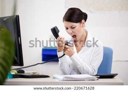 Angry woman shouting at phone - stock photo