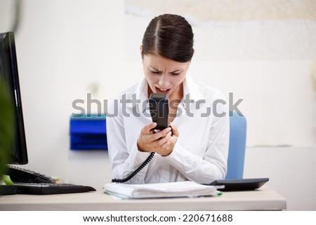 Angry woman shouting at phone - stock photo
