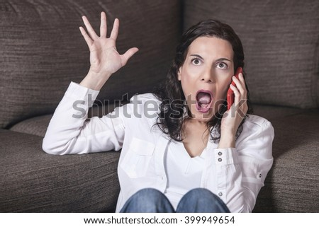 Angry woman shouting on the phone. Toned image with shallow depth of field - stock photo