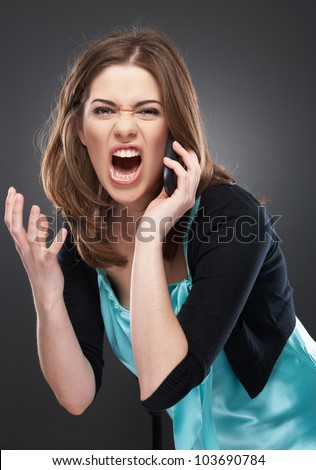 angry woman shouts in phone. Negative emotions on a face. Studio female portrait - stock photo