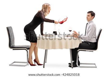 Angry woman spilling her drink on a man and yelling at him on a restaurant table isolated on white background - stock photo