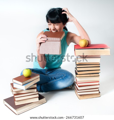Angry woman student bite a book and sitting with apple
