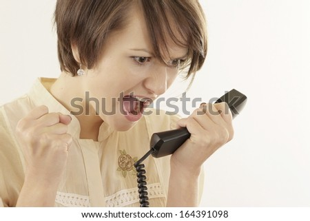 Angry woman talking on the phone on a beige - stock photo