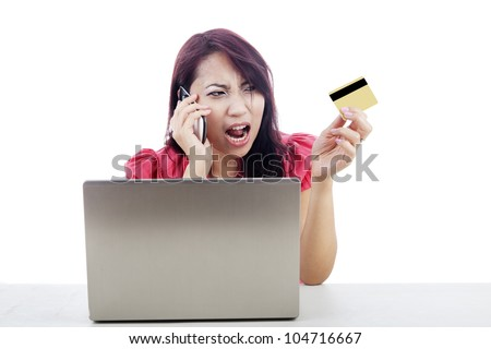 Angry woman talking on the phone with laptop and holding credit card
