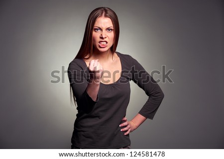 angry woman threatening the fist over grey background - stock photo