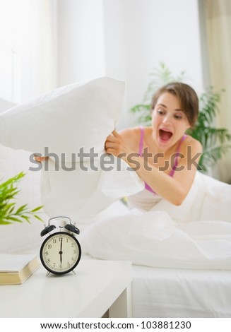 Angry woman trying to break alarm clock by pillow - stock photo