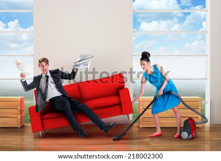 Angry woman vacuuming while man is resting