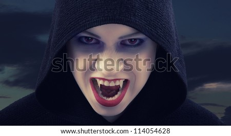 angry woman vampire against the dark sky - stock photo