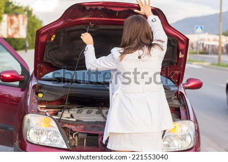 Angry woman waits for assistance with her car broke down on the road side - stock photo
