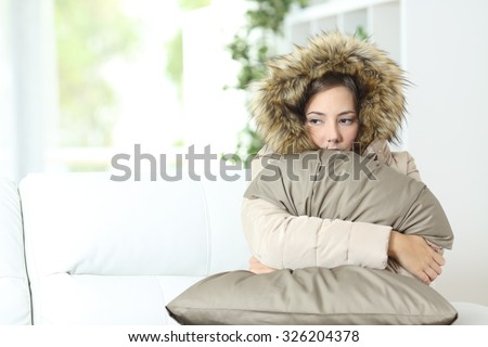 Angry woman warmly clothed in a cold home sitting on a couch - stock photo