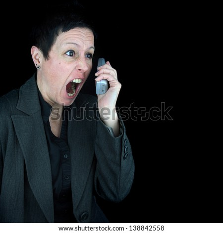 angry woman wearing a suit jacket, shouting during a telephone conversation, against black background - stock photo
